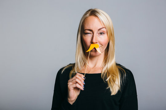 Blonde woman  holds a photobooth in the form of a mustache near her lips on  grey background.
