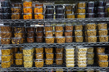 Pile of various dried fruit and nuts packaged in airtight transparent plastic containers for convenience and freshness, positioned on a metal rack or shelf at the supermarket