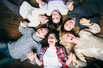Happy friends lying together in circle looking at camera, keeping hands  and smiling while lying on wooden floor.. Concepts about friendship,lifestyle,unity,business and teamwork.