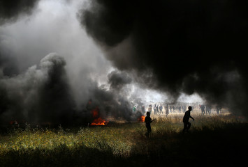 Smoke rises from burning tires as Palestinian demonstrators are seen during clashes with Israeli troops at the Israel-Gaza border at a protest demanding the right to return to their homeland, in the southern Gaza Strip