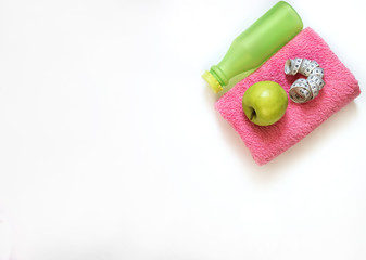 Fitness accessories on a white background. Sneakers, bottle of water, earphones and dumbbells.