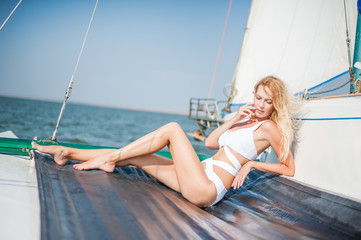 woman in fashion white swimsuit sitting on yacht