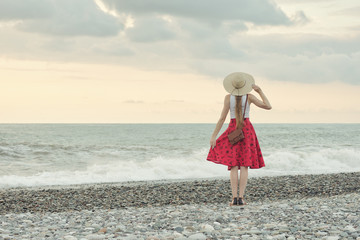 Girl in red skirt and hat standing by the sea, sunset. Back view