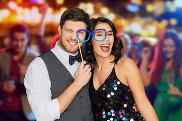 celebration, fun and holidays concept - happy couple posing with party glasses over night club lights background