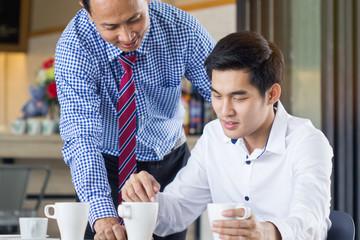 Asian senior businessman describe jobs to intern employee.