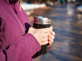 girl warms her hands with a mug with a hot drink in cold weather. Two hands of a girl, holding a hot cup of tea or coffee. concept of an active holiday in cold season