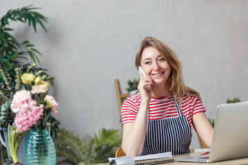 Photo of florist girl talking on phone while sitting at table with computer