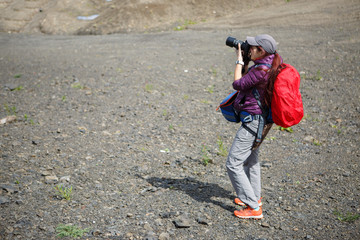 Photo of woman with backpack and camera on hill