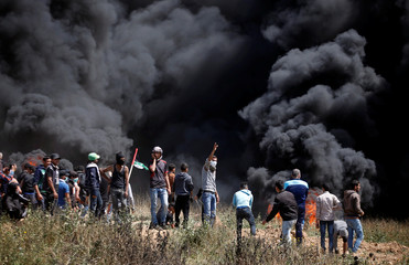 Palestinian demonstrators gather at the Israel-Gaza border during clashes with Israeli troops at a protest demanding the right to return to their homeland, east of Gaza City