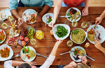 eating, food and leisure concept - group of people sharing green beans at table