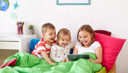 childhood, technology and family concept - little kids with tablet pc computer in bed at home