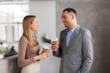 business, people and corporate concept - happy smiling businesswoman and businessman drinking coffee at office