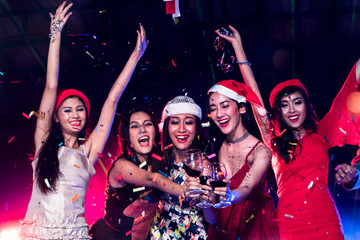 Group of happy young lady dancing together at nightclub with smoke and laser light. Friends celebrates new year together and disc jockey mixing music on background.