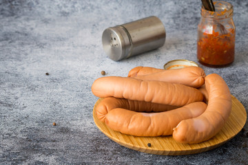 Fresh veal sausages on a round wooden board, next to small jars with seasoning and spices on a blue background with copy space.