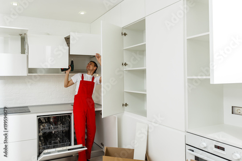 Handyman fixing kitchen s cabinet with screwdriver