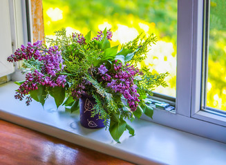 Bouquet of lillac or syringa vulgaris flowers in a window sill