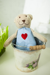 Toy bear with a heart sits in a bucket
