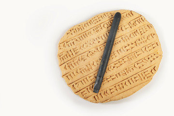 Ancient type of Akkad empire style cuneiform writing in brown clay with writing tools