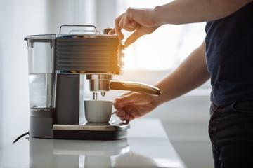 A man prepares espresso for a coffee maker