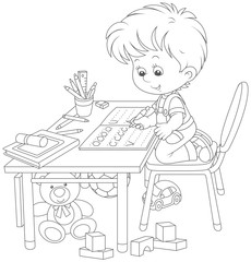 Little boy doing his homework in an exercise book with samples of writing, a black and white vector illustration in a cartoon style