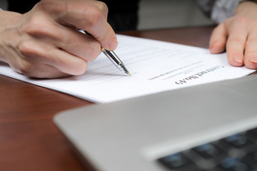 A businessman puts his signature on the contract. Copy space.