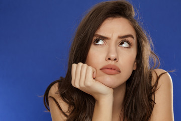 thoughtful young frowning woman on blue background