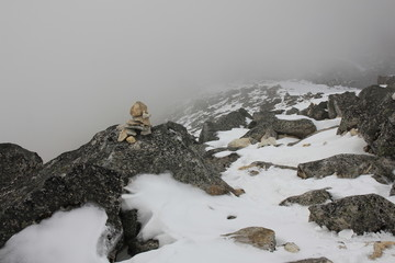 Cairn marking the path to the top of mount Tserko Ri, Langtang National Park. Mountain ridge on a fogy spring day.