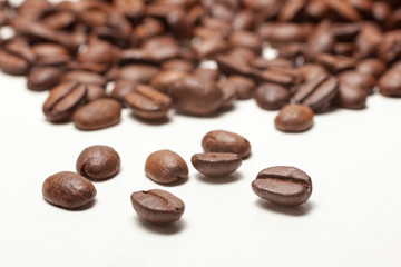 Spilled coffee beans on white background,