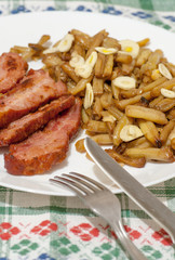 Fototapete - green beans with slices of fried bacon and decorated with slices of garlic on white plate on decorated tablecloth