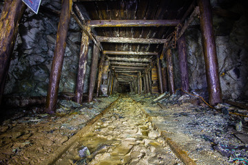 Underground abandoned gold ore mine shaft tunnel gallery with wooden timber
