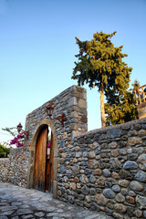 mediterranean style stone wall and wooden door