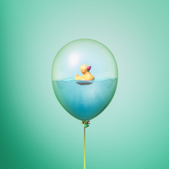 Minimal balloon concept with toy duck on water. Yellow rubber duck idea on green background