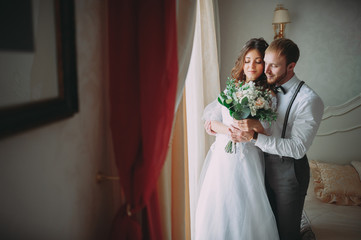 stylish groom with beard and beautiful bride posing in hotel