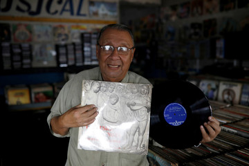 """Jose Roberto Reyes, owner of """"El Pollo Musical"""" (The Musical Chicken) record store poses for a picture in San Salvador"""