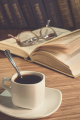 A cup of coffee and an open book on the table