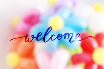 welcome lettering on blurred flowers background