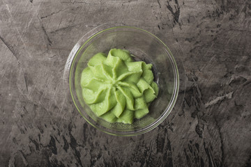 Bowl with wasabi on a black concrete background, top view
