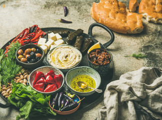 Mediterranean, Middle Eastern meze starter platter. Stuffed pickled paprikas, dolma, hummus, spiced oil, olives, sundried tomatoes, nuts, cheese, flatbread on tray, selective focus. Party food concept