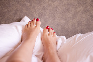 Feet of woman with red painted nails on the bed