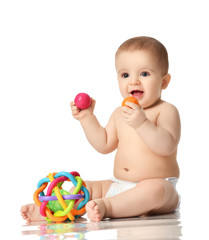 Infant child baby boy toddler sitting in diaper playing with balls and plastic toys isolated