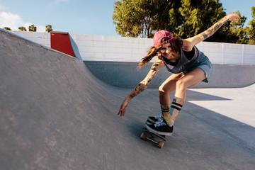 Woman practising skateboarding at skate park