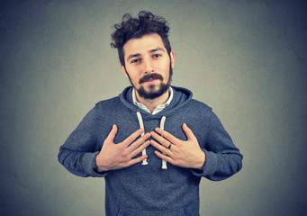 Faithful man keeps hands on chest near heart, shows kindness expresses sincere emotions