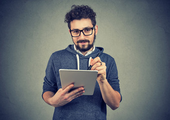 Hispter man in glasses holding tablet computer and pen looking at camera