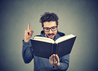 Excited hipster guy reading a book