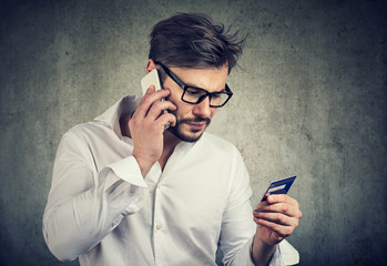 Man making call holding credit card