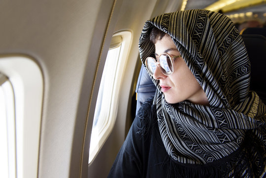 Beautiful woman looking out of airplane window