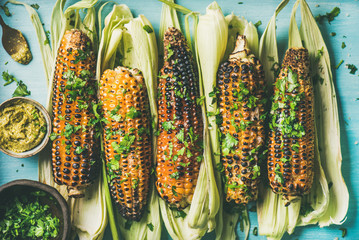 Summer vegan dinner or snack. Flat-lay of grilled sweet corn with smoked sea salt, cilantro and pesto sauce over blue background, top view. Vegetarian, healthy, clean eating, alkaline diet concept