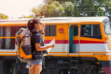 Young asian woman traveler with backpack and sunglass looking the map with train background at Ayutthaya train station.