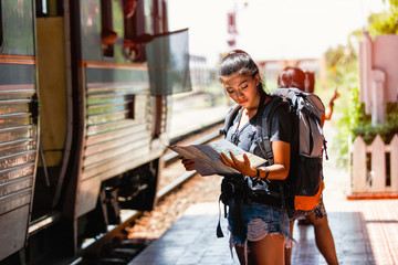 Young asian woman backpacker and traveling looking map for travel at ayutthaya train station background, Ayutthaya Province, Thailand Wall mural