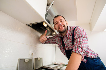 Handsome guy work on ventilation in the kitchen
